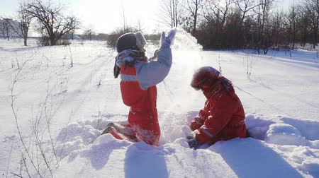 sourozenci : Two funny kids throwing snow together