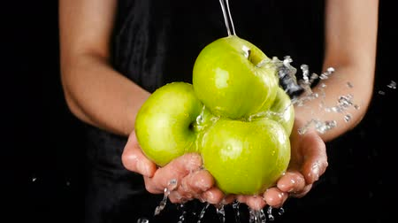 Washing the green apples in woman hands, slow motion
