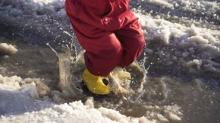gumboots : Kid in rainboots jumping in the ice puddle, slow motion