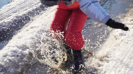 gumboots : Boy in rainboots jumping in the ice puddle, slow motion