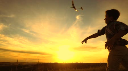 toy : Silhouette of boy launching his airplane against sunset