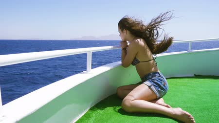 Adorable girl looking to the blue sea from yacht board