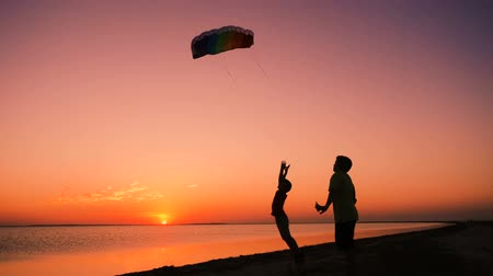 Two kids launching the rainbow kite together at sunset