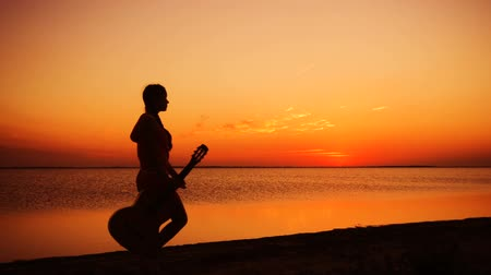 Young girl walking with guitar on the beach at sunset Wideo