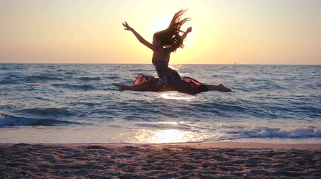 derű : Beautiful girl jumping on the sea coast at sunrise