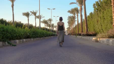 Young girl walking on the road with palm trees