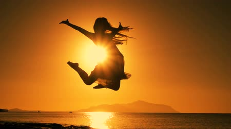 silhouette of girl jumping at sunrise on the beach
