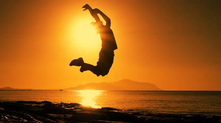 silhouette of boy jumping at sunrise on beach Стоковые видеозаписи
