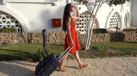 voyager : Young girl in red dress traveling on street with suitcase Stock Footage