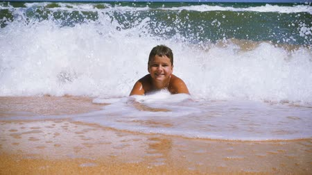 Smiling boy lying on the beach at the surf