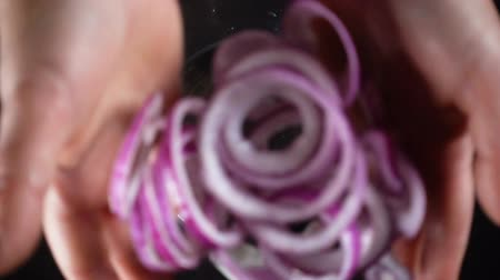 Falling red onion cuts in glass bowl, slow motion Wideo