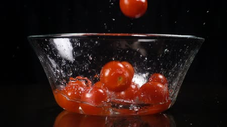 Falling cherry tomatoes in glass bowl, slow motion