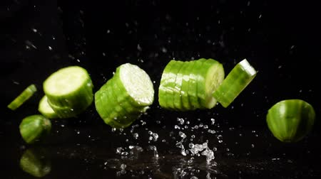 Falling cucumber cuts with water splash, slow motion