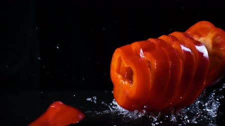 Falling red paprika cuts with water splash, slow motion Wideo