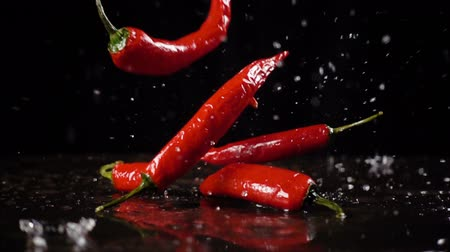 Falling red  chili pepper with water splash, slow motion Wideo