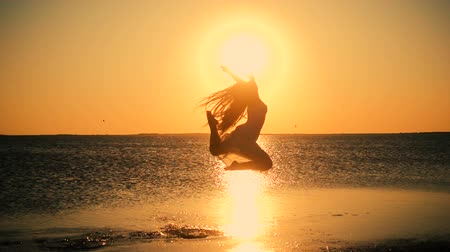 Beautiful girl jumping on the lake coast at sunset, Genichesk, U