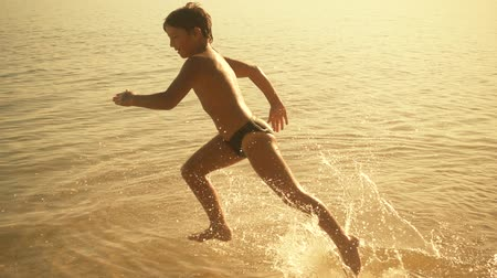 boy running on the water with splashes