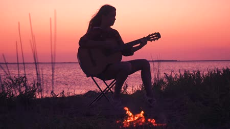 Young girl playing guitar on the beach with campfire at sunset