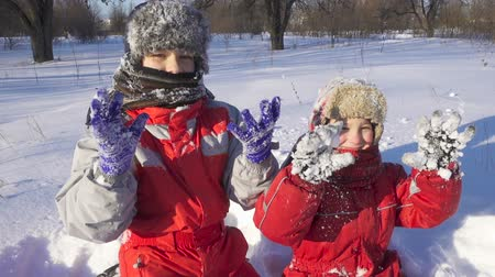 sourozenci : Two kids on winter park show sticky snow glowes