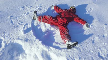 Happy kid on winter park making snow angel