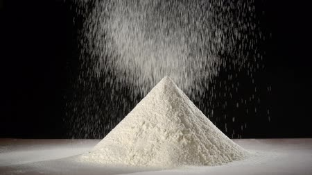 準備する : sifts flour through a sieve on the flour heap, slow motion