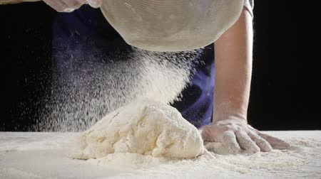 zástěra : womans hands sifts flour through a sieve on the dough, slow mot