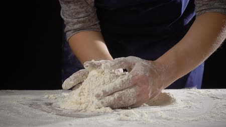 womans hands kneading the dough on the table