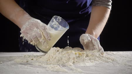 womans hands pour the milk to dough for kneading Wideo