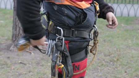 spona : high-rise worker fastens a carabiner on the safety belt