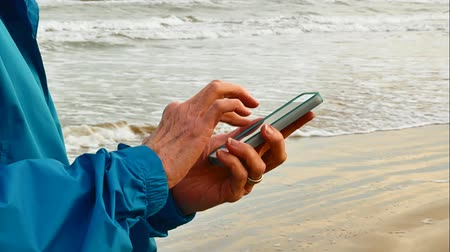holding onto : Smart phone being used at ocean beach as waves roll onto sandy shore