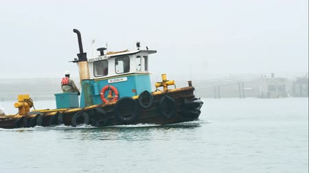 bolsa : Port Aransas, Texas USA - February 10 2018: Old tug boat hauls bags on a fogy morning Stock Footage