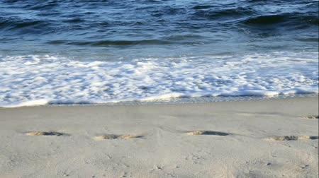 pegadas : Beach scene with waves and foot prints on a sunny late afternoon Stock Footage