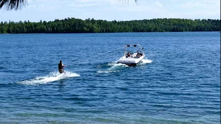 лыжник : Water skier and speed boat on beautiful northern Minnesota lake on sunny day
