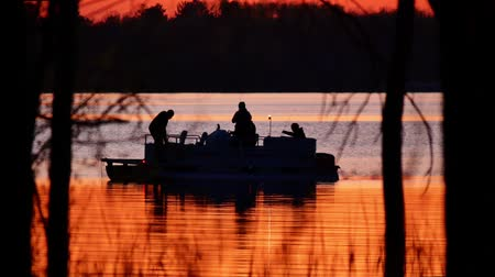 pontoon : Silhouette of family in pontoon, fishing on Lake Irving at sunset in Bemidji, Minnesota.