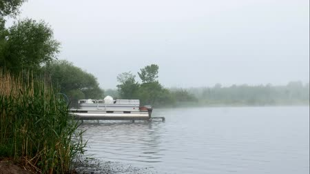 pontoon : Early morning fog on Lake Irving with pontoon boat on boatlift in Bemidji Minnesota
