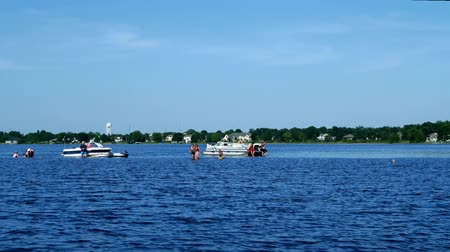 pontoon : Bemidji, MN USA - June, 2018: Landscape view of beach on the south shore of Lake Bemidji in Minnesota on a sunny day taken from moving boat on lake Stock Footage