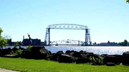 superior : Duluth, Minnesota - July 2, 2018: Aerial Lift Bridge and Canal to Harbor with children on boulders on a sunny morning - zoom in