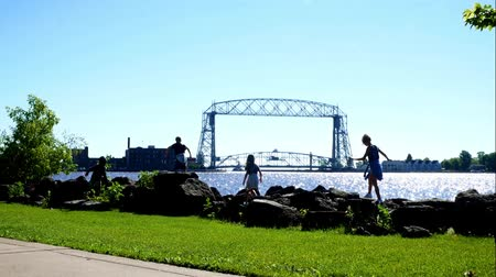 arquipélago : Duluth, Minnesota - July 2, 2018: Aerial Lift Bridge and Canal to Harbor with children on boulders on a sunny morning