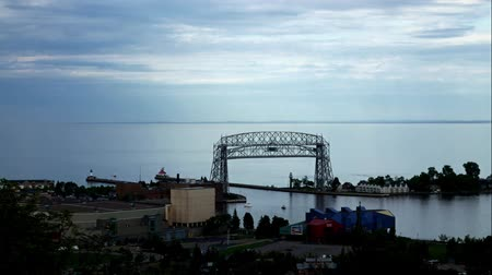 passagem : Time lapse of iron ore ship going under the historic aerial lift bridge in Duluth, Minnesota under cloudy skies, leaving Lake Superior and entering Duluth Harbor.