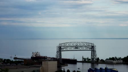 superior : Time lapse of iron ore ship going under the historic aerial lift bridge in Duluth, Minnesota under cloudy skies, leaving the Great Lake Superior and entering Duluth Harbor.