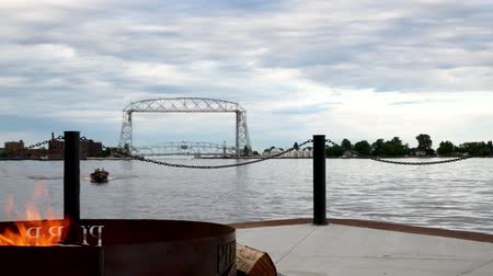 superior : Duluth, Minnesota - July 2, 2018: Iconic aerial lift bridge, firepit and fishing boat on cloudy morning