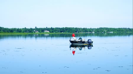 outdoor hobby : Bemidji, MN - July 30, 2018: Fisherman in fishing boat enjoying a beautiful morning on Lake Irving