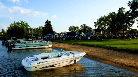 pontoon : Bemidji, Minnesota - August 29, 2018: Lakeside evening concert with crowd and boats on shore Stock Footage