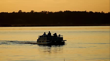 szórakozási : Silhouette of people enjoying boating on a calm lake in Bemidji, Minnesota at sunset. Pontoon, fishing boat & speed boat with wake boarder. Stock mozgókép