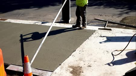 kielnia : Workman finishes and smooths concrete surface on new sidewalk on sunny day