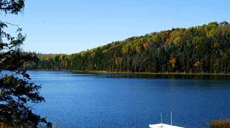 lakeshore : Blue sky with sunshine over beautiful serene remote northern Minnesota lake with autumn colors, boat, dock and new snow