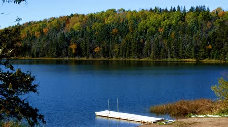 Blue sky with sunshine over beautiful serene remote northern Minnesota lake with autumn colors, boat, dock and new snow