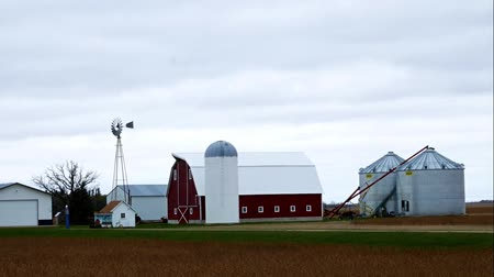 навес : Farm buildings with active windmill on a cloudy day in Minnesota - includes barn, granary, sheds, bean field and grain auger.