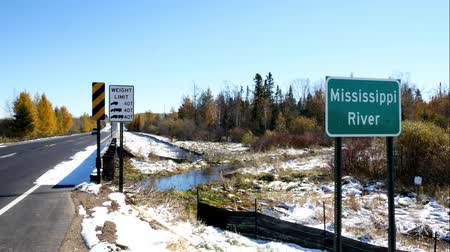 Mississippi River flowing north near its source at Itasca State Park in Minnesota. A car drives by this sign at the fifth highway bridge over the Mississippi River after an early autumn snowfall.