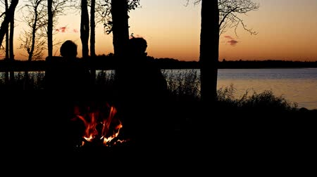 Silhouette of people enjoyiing beautiful lakeside campfire just after sunset with trees along shoreline and ripples on northern Minnesota lake